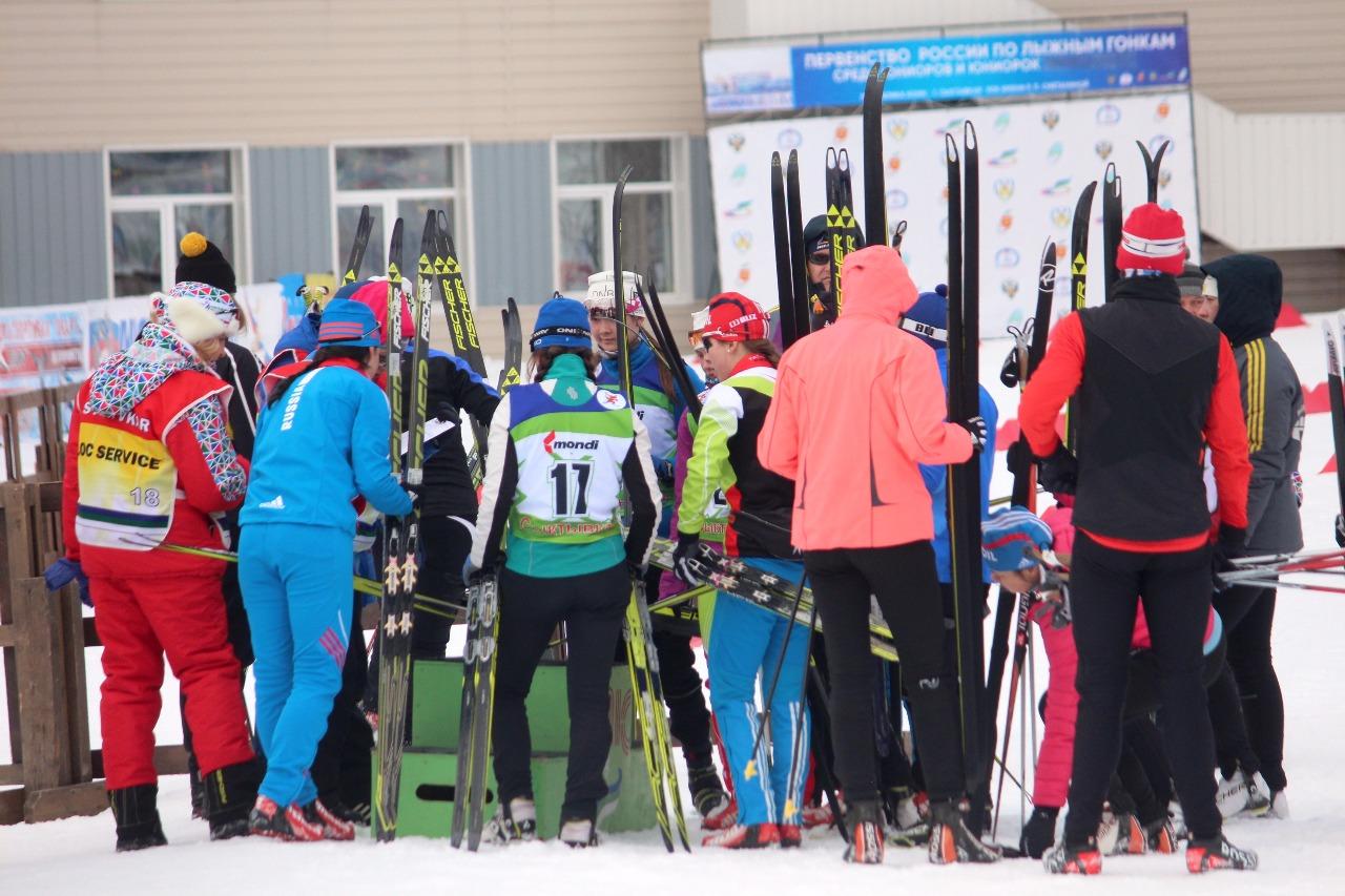 Спортсменки по очереди проходят чипование и маркировку лыж.