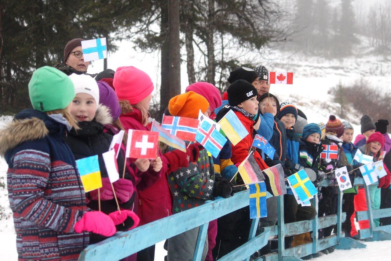 Юные финские болельщики с международными флажками в руках пришли поприветствовать участников первой в этом сезоне международной лыжной гонки.