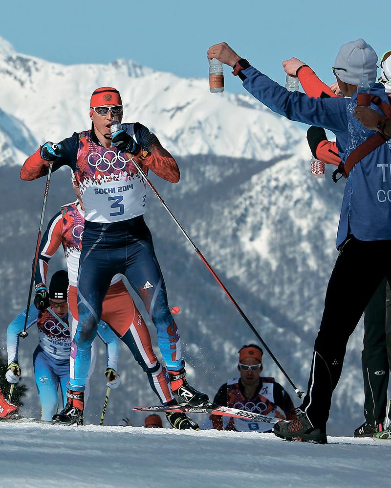 Чтобы поддерживать высокую работоспособность на 50-километровой дистанции, необходимо постоянно пить спортивный напиток, что и делает на этом фото Александр Легков, возглавляющий в данный момент пелотон